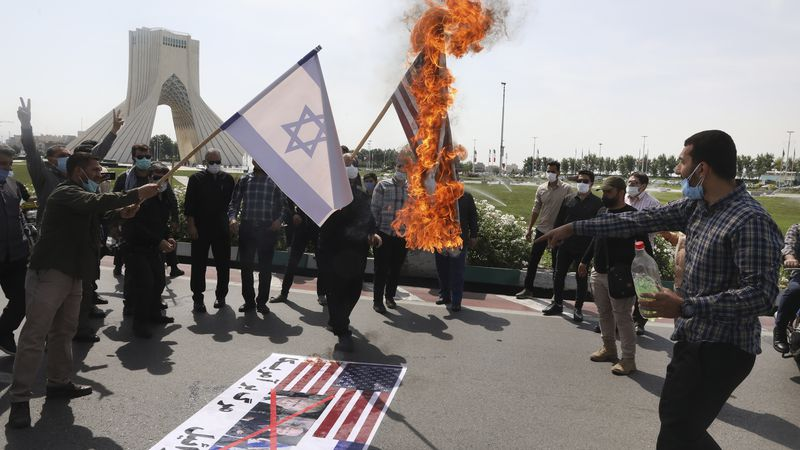 Demonstrators burn representations of Israeli and U.S flags during the annual Al-Quds, or...