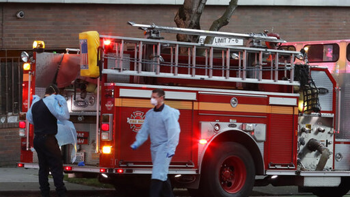 Seattle firefighters wearing masks, gowns, and gloves to protect against the transmission of...