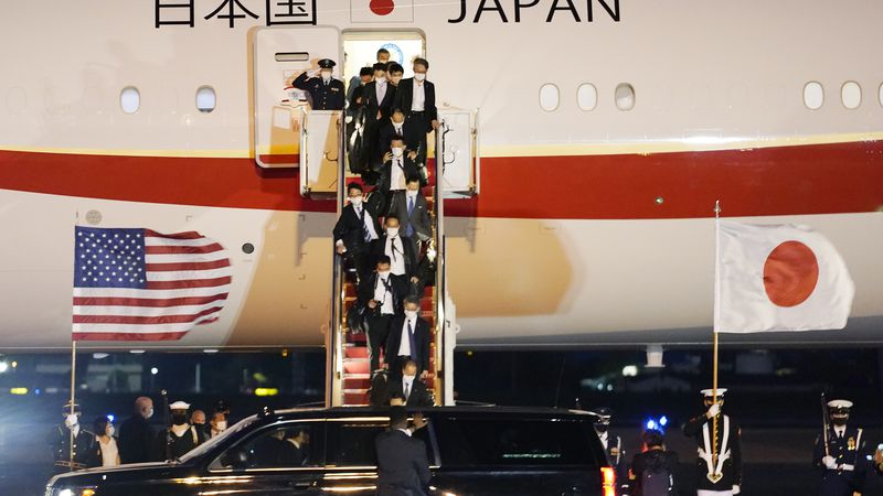 The Japanese delegation walks off the plane after Japanese Prime Minister Yoshihide Suga...