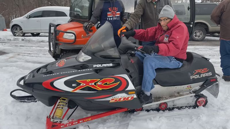 Grandpa Miller drives snowmobile for the first time.