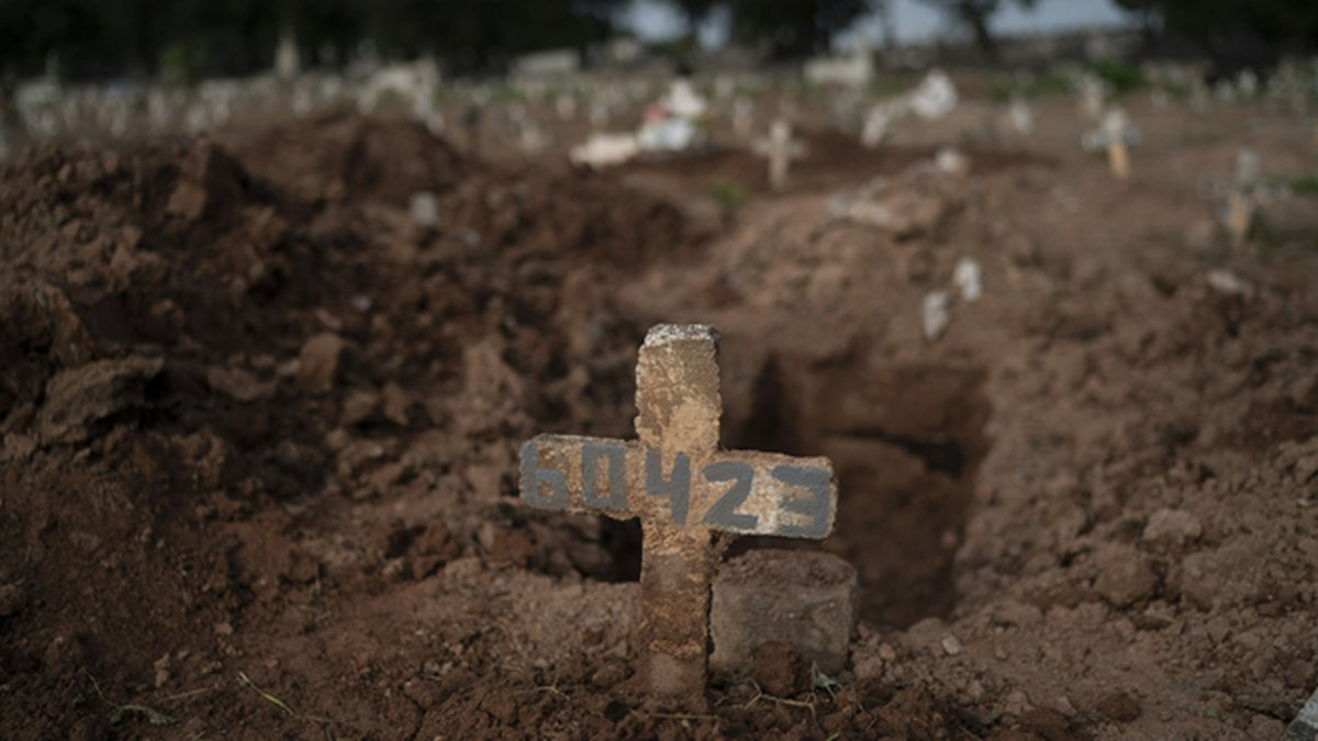 A cross marks the grave of 57-year-old Paulo Jose da Silva, who died from the new coronavirus,...
