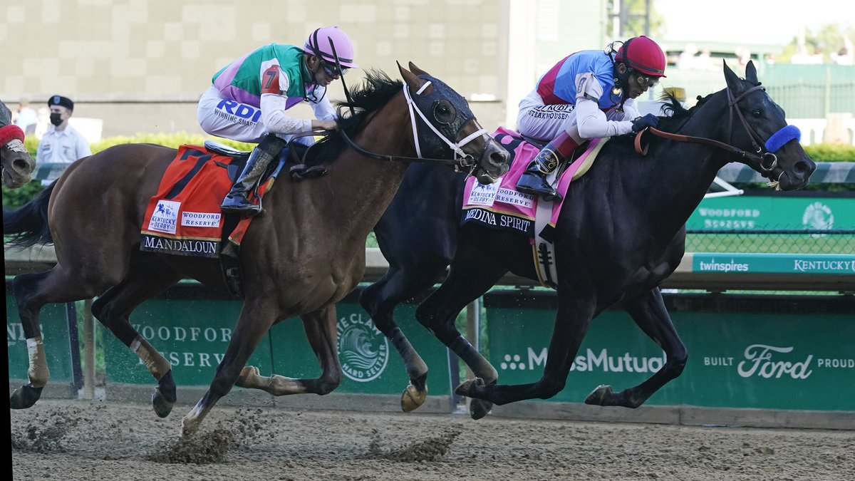 John Velazquez, right, rides Medina Spirit ahead of Florent Geroux aboard Mandaloun to win the...