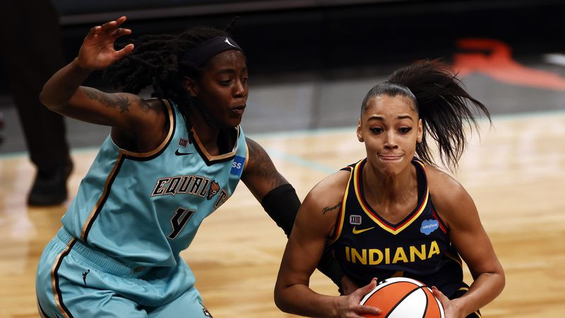 Indiana Fever guard Kysre Gondrezick (4) drives past New York Liberty guard Jazmine Jones (4)...