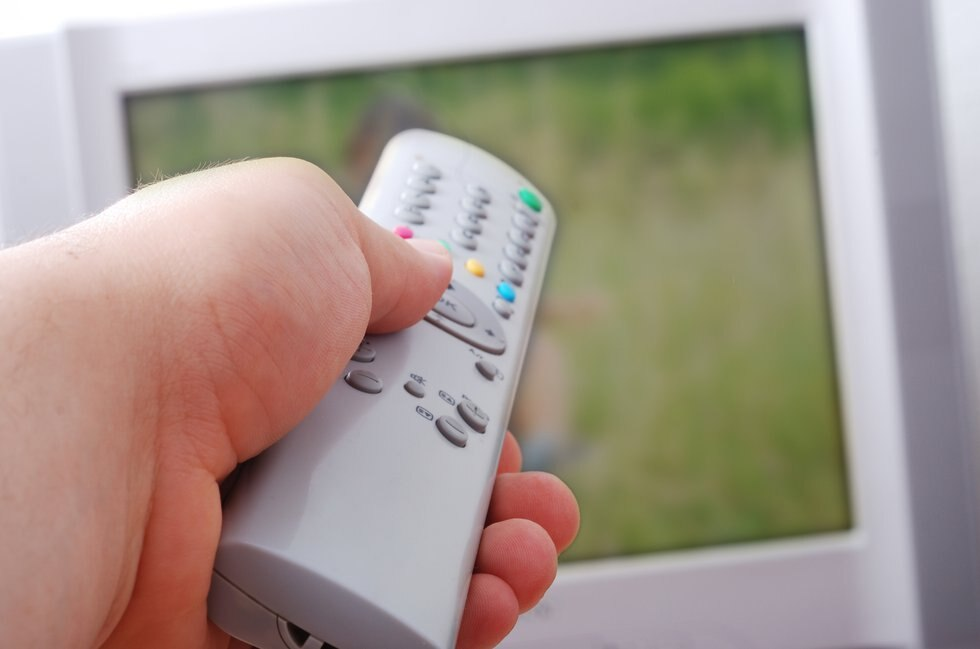 Remote control used by adult man in his hand