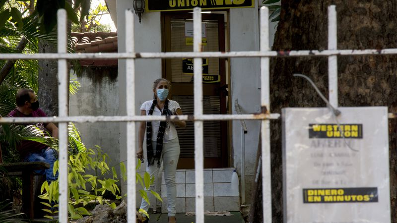 A woman waits to be attended at a Western Union office on its last day of business in Havana,...